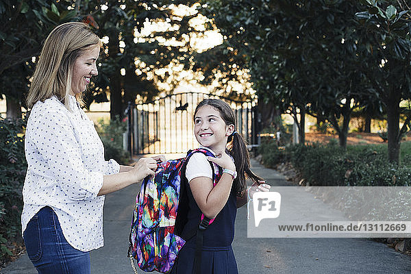 Seitenansicht der Mutter  die den Rucksack der Tochter öffnet