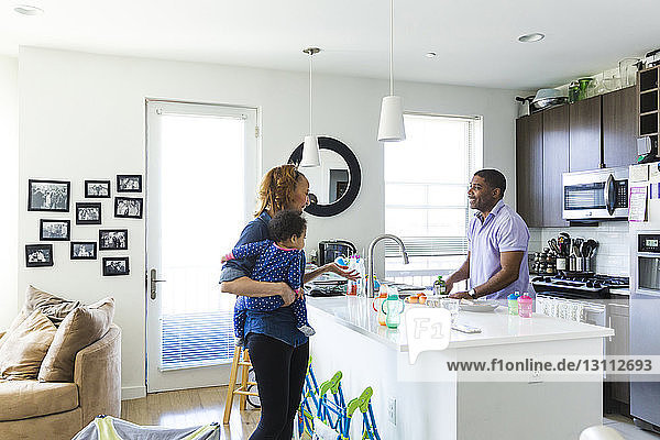 Man looking at woman carrying baby girl while standing in kitchen