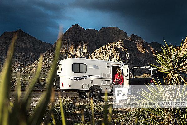 Frau steht am Wohnwagen gegen Berge und Himmel