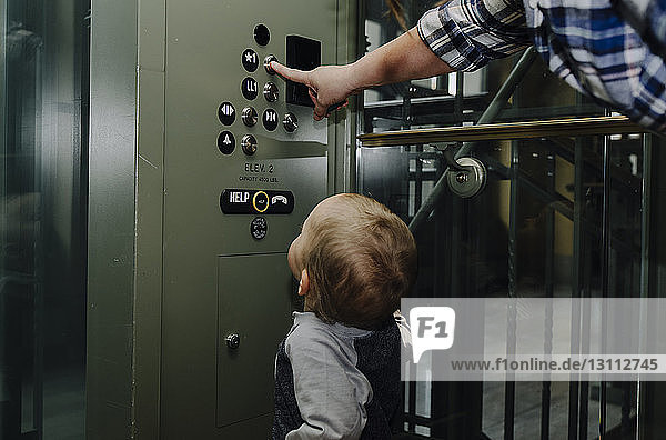 Sohn sieht die Mutter an und drückt den Fahrstuhlknopf