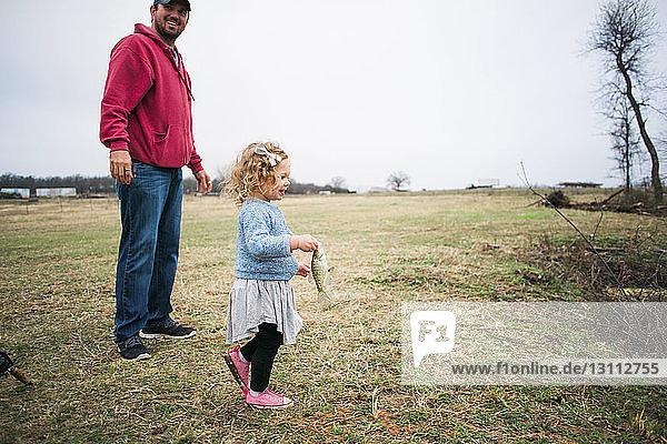 Fröhliche Tochter hält Fisch  während sie mit dem Vater auf einem Grasfeld fischt