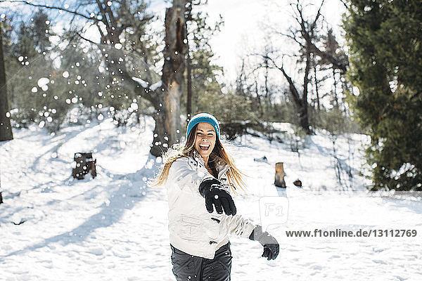 Frontansicht einer fröhlichen Frau  die mit Schnee auf dem Feld spielt