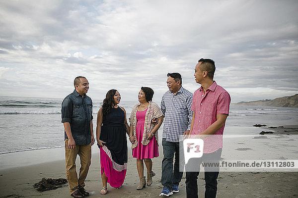 Glückliche Familie beim Strandspaziergang am Strand gegen den Himmel
