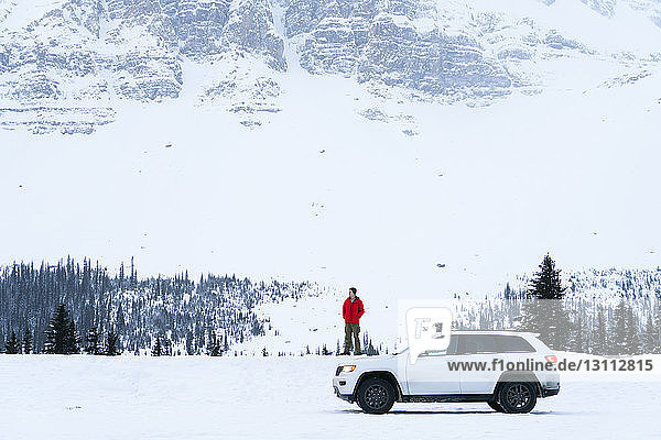 Hiker standing on snow covered field by off-road vehicle during winter