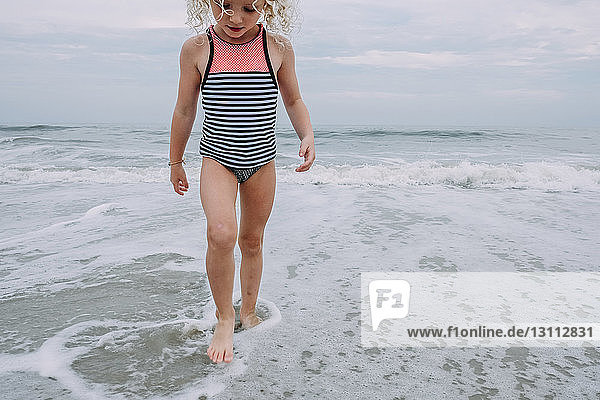 Girl playing in waves at Cape May Beach against sky