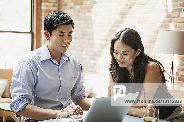 Couple using laptop computer while sitting at table