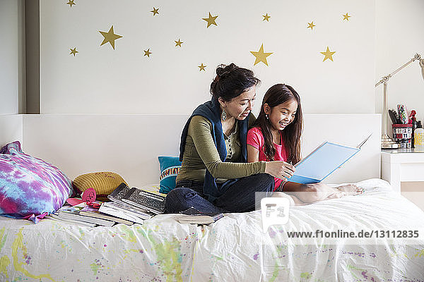 Mother and daughter reading book while sitting on bed at home