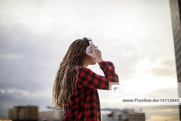 Seitenansicht einer Frau  die Kopfhörer trägt  während sie gegen den Himmel steht