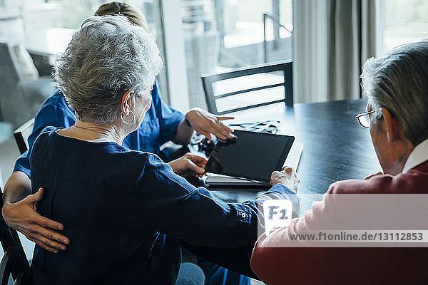Hausangestellte diskutiert am Esstisch am Tablet-Computer mit einem älteren Paar