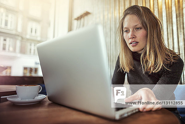 Junge Frau mit Laptop am Café-Tisch