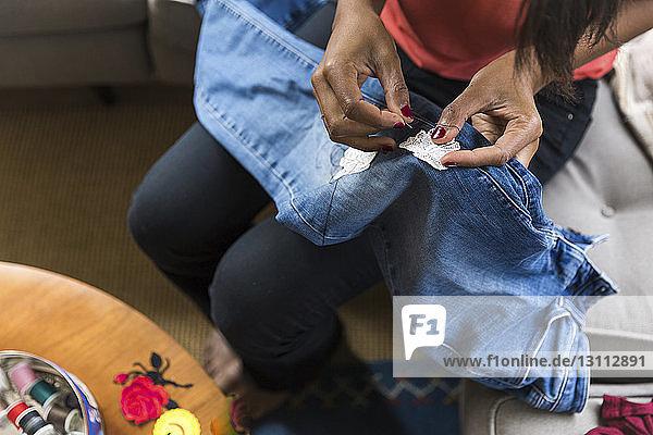 Schrägansicht einer Frau  die zu Hause auf dem Sofa sitzend Textilpatch auf Jeans näht