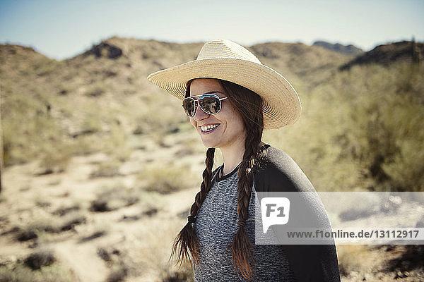 Glückliche Frau mit Sonnenhut steht im Sommer auf Berg