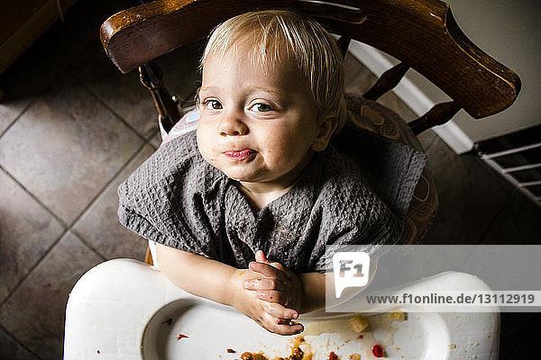 Porträt eines unordentlichen niedlichen Jungen auf einem Stuhl sitzend