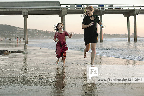Playful mother and daughter running at beach