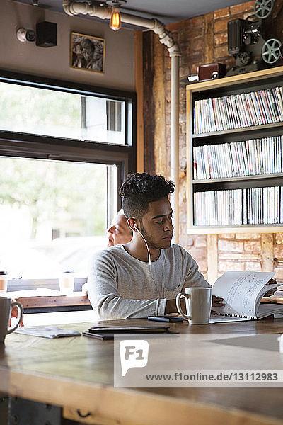 Mann hört Musik  während er im Café ein Buch liest