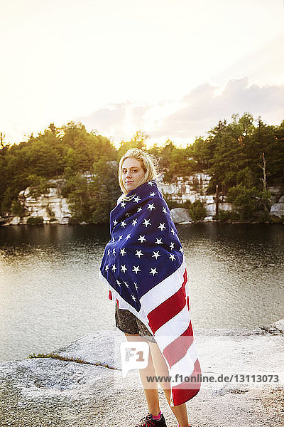Portrait of woman wrapped in American flag standing on rock overlooking lake