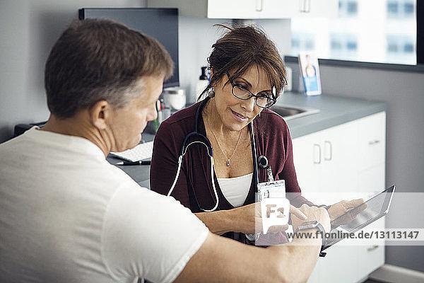 Männlicher Patient zeigt auf Armbanduhr  während er mit einer Ärztin in der Klinik diskutiert