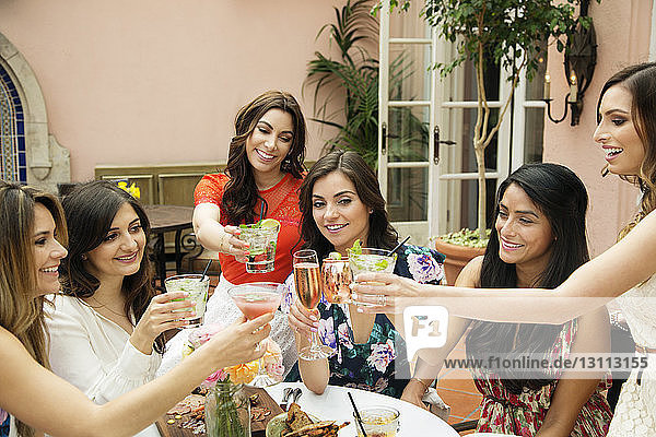 Freundinnen stoßen im Freiluftrestaurant auf Getränke an