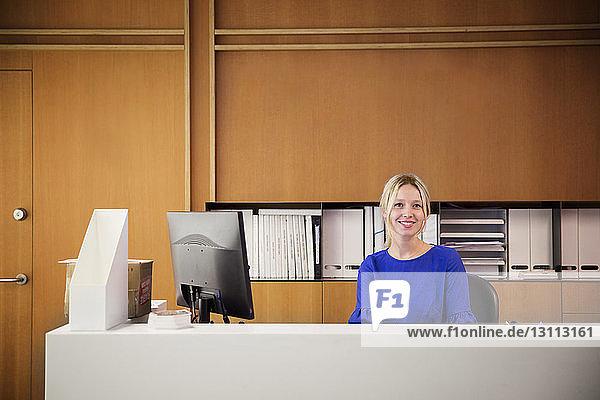 Porträt einer lächelnden Geschäftsfrau  die am Desktop-Computer im Büro sitzt