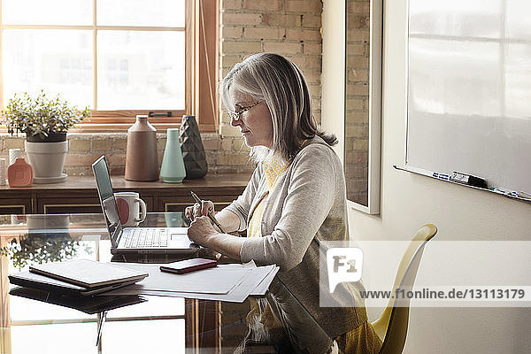 Side view of mature businesswoman using laptop in creative office
