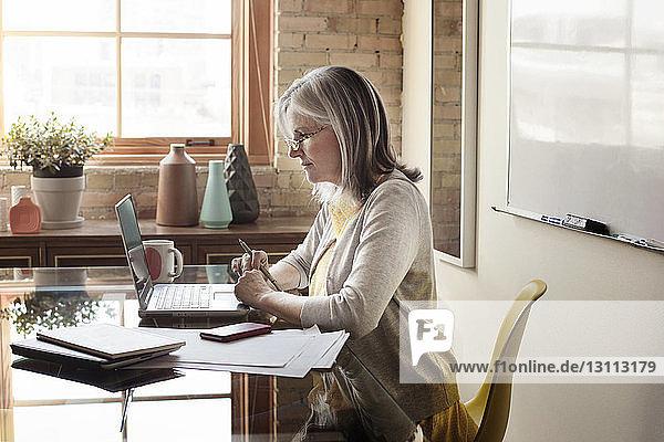 Seitenansicht einer reifen Geschäftsfrau mit Laptop im Kreativbüro