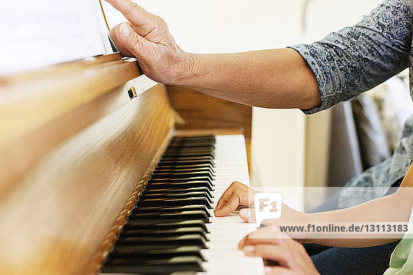 Grandmother assisting granddaughter in playing piano at home