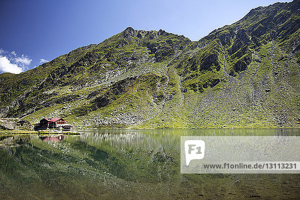 Reflection of house and mountain in lake against sky