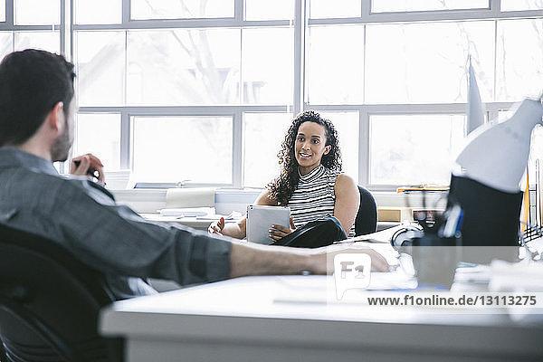 Geschäftsfrau hält Tablet-Computer in der Hand und diskutiert mit männlichem Kollegen am Schreibtisch im Büro