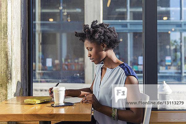 Seitenansicht einer Frau  die in einem Notizblock im Straßencafé schreibt