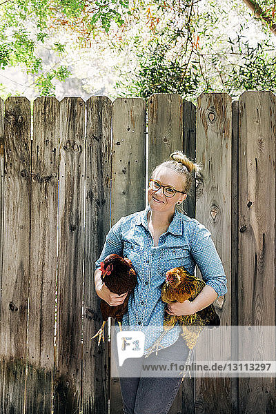 Portrait of smiling woman carrying chickens against wooden fence