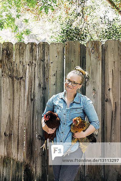 Porträt einer lächelnden Frau  die Hühner gegen einen Holzzaun trägt