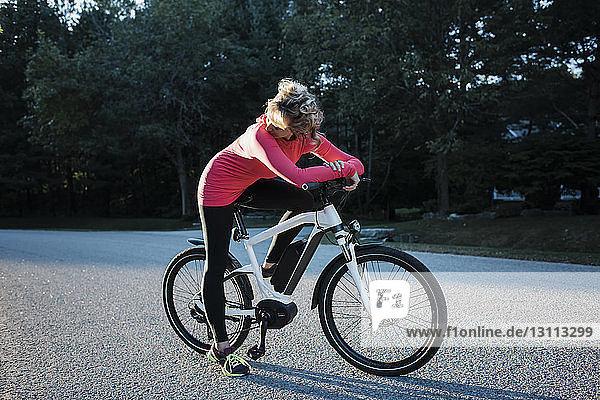 Frau schaut weg  während sie auf dem Mountainbike an der Landstraße sitzt