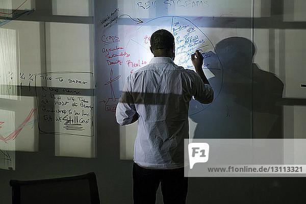 Rückansicht eines Geschäftsmannes  der auf einem Whiteboard über einem Tablet-Computer im Büro schreibt