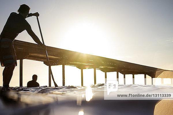 Silhouetten-Mann paddelt auf dem Meer bei klarem Himmel am sonnigen Tag Silhouetten-Mann paddelt auf dem Meer bei klarem Himmel am sonnigen Tag