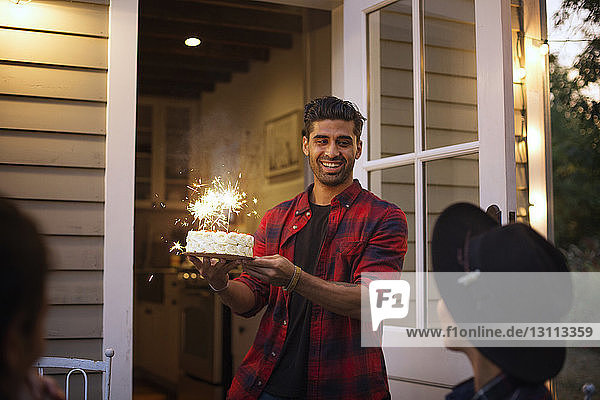 Happy man holding birthday cake with sparklers