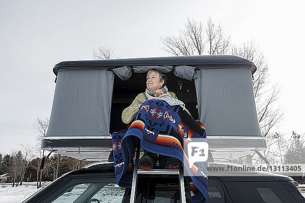 Woman knitting while sitting in roof tent on car during winter
