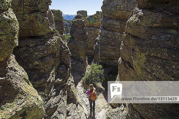 Hochwinkelaufnahme einer Frau mit Rucksack  die an einem sonnigen Tag inmitten von Felsen steht
