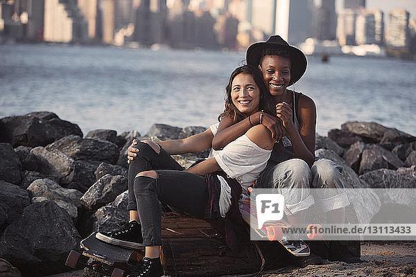 Freundinnen umarmen sich  während sie mit Skateboards am felsigen Ufer sitzen