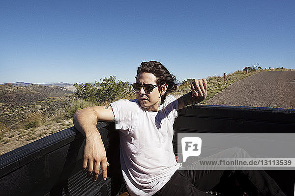 Young man looking away while traveling in pick-up truck against clear sky