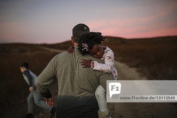 Rückansicht eines Vaters  der seine Tochter trägt  während er bei Sonnenuntergang auf einem Feldweg geht