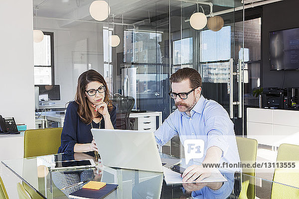 Ältere Geschäftskollegen  die gemeinsam im Sitzungssaal einen Laptop benutzen