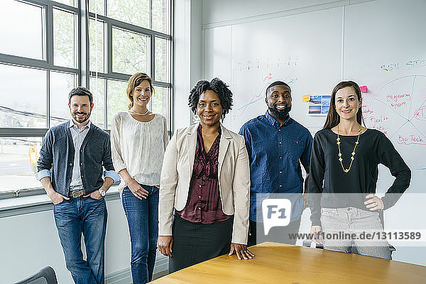 Portrait of confident smiling business people standing by table in office