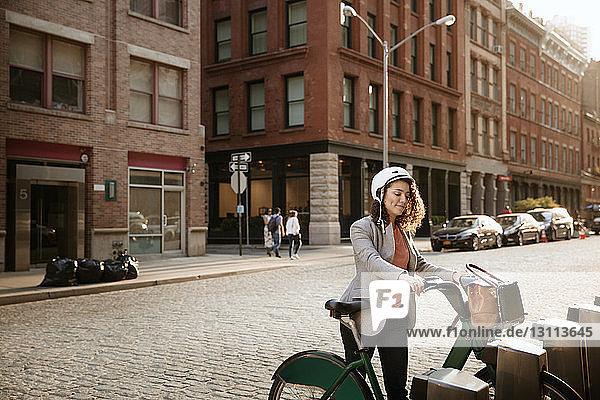 Geschäftsfrau mit Fahrrad auf dem Parkplatz an der Straße