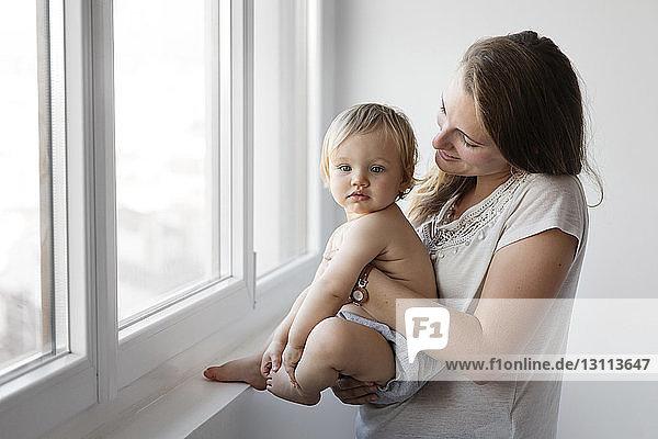 Seitenansicht einer Mutter  die eine Tochter trägt  während sie zu Hause am Fenster steht