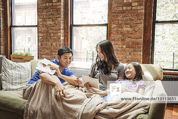 Girl showing tablet computer to parents while sitting on sofa at home