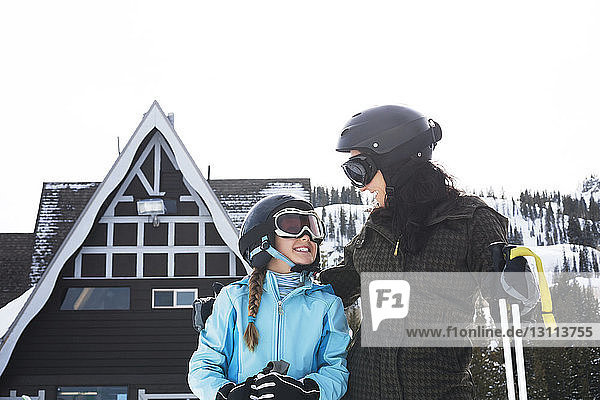 Happy mother and daughter standing at ski resort against sky