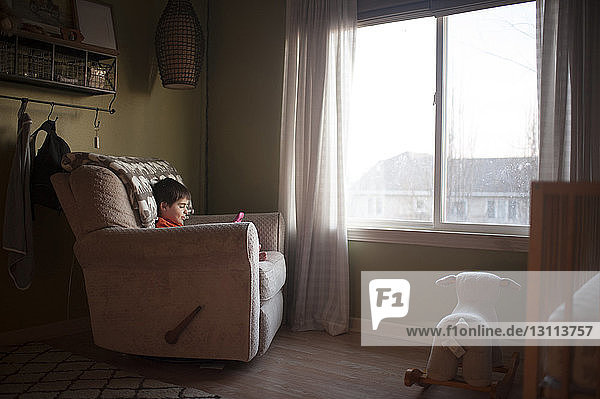 Boy playing with toy while sitting on chair by window at home