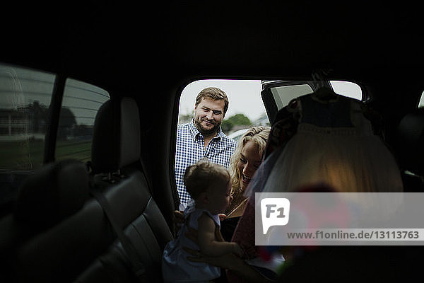 Smiling parents looking at baby girl in car