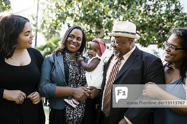 Glücklicher älterer Mann mit Familie steht im Park