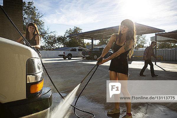 Female friends washing camper van on street